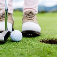 Close up of feet of golfer, golf club and ball beside hole