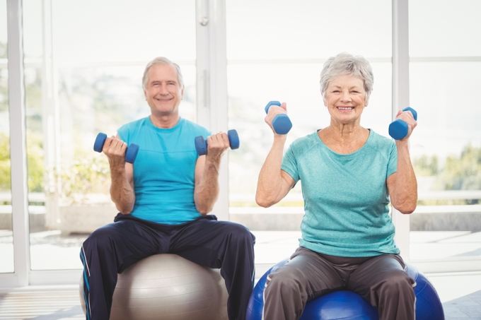 Senior couple holding dumbbells while sitting