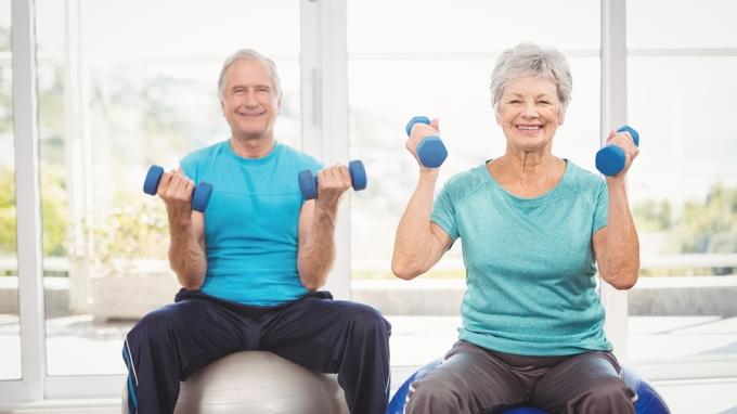 Senior couple holding dumbbells while sitting