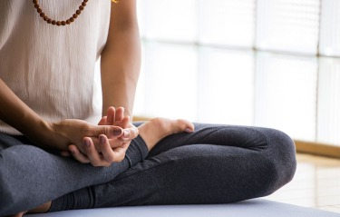 Woman's hands, legs and feet, in seated meditation position.